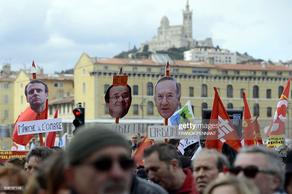 People hold placards picturing (from L-R) French Economy and Industry minister Emmanuel Macron, French President Francois Hollande and head of French employers' association MEDEF Pierre Gattaz as they demonstrate in the streets of Marseille during the traditional May Day rally on May 1, 2016. / AFP / Franck PENNANT