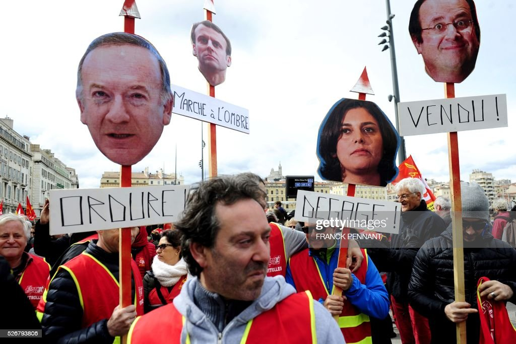 People hold placards picturing (from L-R) the head of French employers' association MEDEF Pierre Gattaz, French Economy and Industry minister Emmanuel Macron, French Labour Minister Myriam El Khomri and French President Francois Hollande, as they demonstrate in the streets of Marseille during the traditional May Day rally on May 1, 2016. / AFP / Franck PENNANT