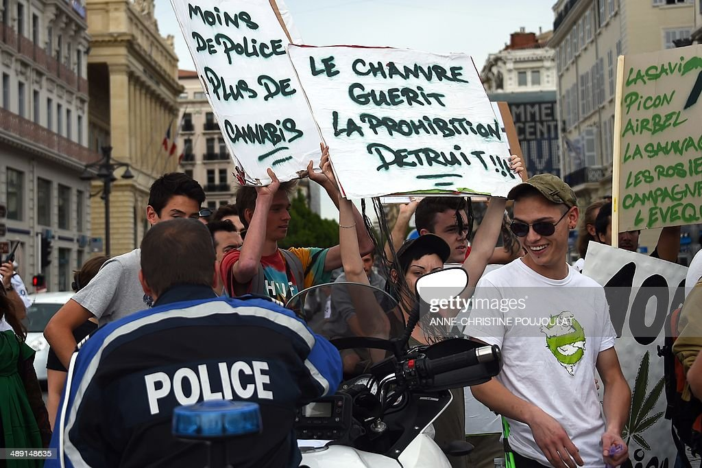 People hold placards reading 'Fewer police officers, more cannabis' (L) and 'Cannabis heals, Prohibition destroys' as they face policemen during a protest to call for the legalization of marijuana on May 10, 2014, at the Old Harbour in Marseille, southern France. About 147 million people globally -- or about 2.5 percent of the population -- use cannabis, according to the World Health Organization.