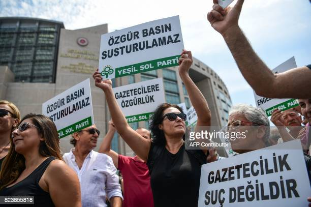 People hold placards reading 'Free media can not be silenced' on July 28 2017 during a demonstration in front of Istanbul's courthouse A Turkish...