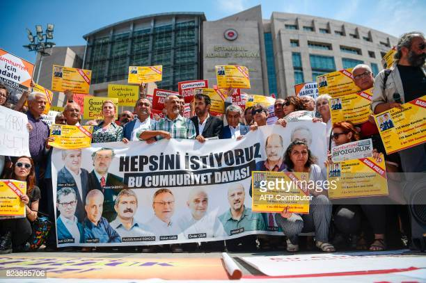 People hold placards reading 'Freedom for journalists we want them all free'on July 28 2017 during a demonstration in front of Istanbul's courthouse...