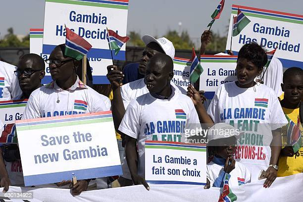 People hold placards reading 'Gambia made its choice save democracy in Gambia save the new Gambia' during a protest in support of Gambia by...