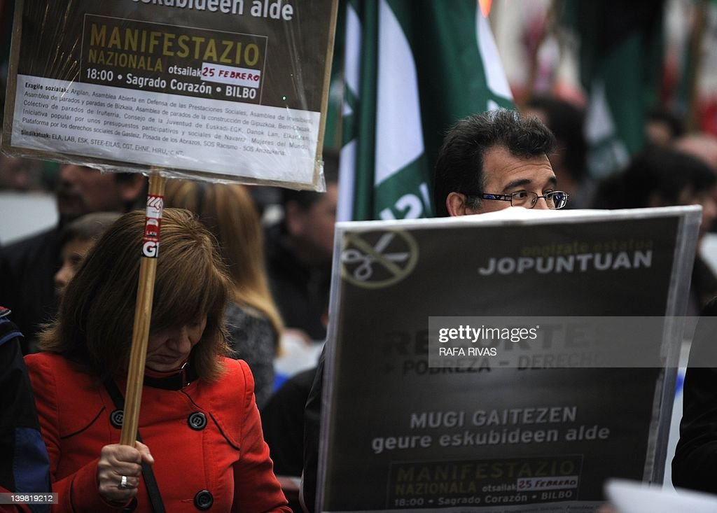 People hold placards reading 'More cuts, more poverty, less rights' during a demonstration against the government's new labour reform and cuts in social services on February 25, 2012 in the Northern Spanish Basque city of Bilbao. The conservative government that took power in December 2011 after a landslide election victory has launched a tough programme of reforms and spending cuts and is pressuring the big-spending regions to do their bit.