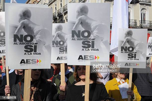 People hold placards reading 'No to abortion yes to life' during an antiabortion demonstration at Puerta del Sol in the center of Madrid on March 25...