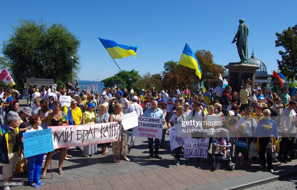 People hold placards reading 'Russians stop maniac Putin!', 'Putin you are drunk. Go home!', 'Putin go home!' and 'My brother is Cain' during a protest against the Russian president in the southern Ukrainian city of Odessa on August 30, 2014. The European Union readied a fresh wave of sanctions against Russia, with warnings that the escalating conflict in Ukraine was putting all of Europe at risk. Fears of a wider confrontation spiralled after NATO said Russia sent troops and weapons across the border to help pro-Kremlin rebels in a new counter-offensive that has seen key towns in the southeast wrested from Kiev's control.