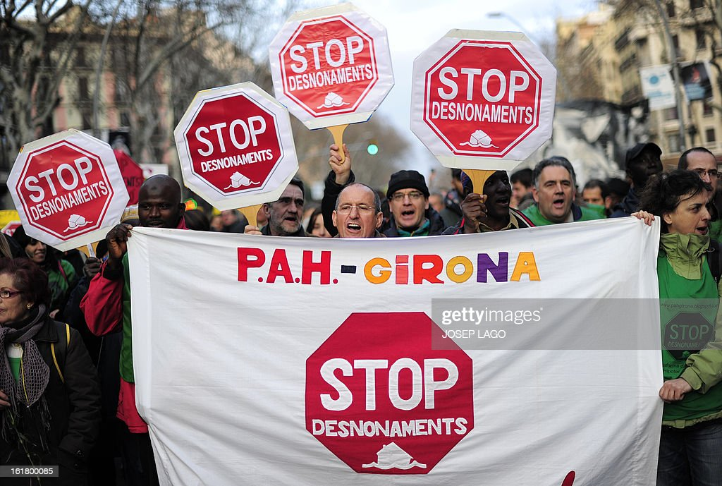 People hold placards reading 'Stop evictions' during a demonstration called by the organisation Platform for Mortgage Victims (PAH) to push for a new law to end a wave of evictions of homeowners ruined by the economic crisis, on February 16, 2013 in Barcelona. Similar protests were called in 50 other Spanish cities, the latest of months of demonstrations driven by anger at Spain's recession and the conservative government, which is imposing austere economic reforms. Campaigners passed a rare milestone on February 12, 2013 when the Spanish parliament agreed to debate a popular bill of measures to protect poor homeowners, backed by a petition that received more than 1.4 million signatures.