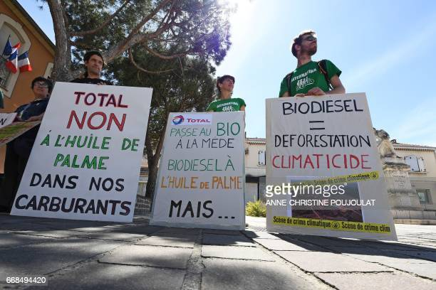 People hold placards reading 'Total no to palm oil in our fuel' 'Total passes to organic at the Mede oil palm biodiesel but' and 'Biodiesel equals...