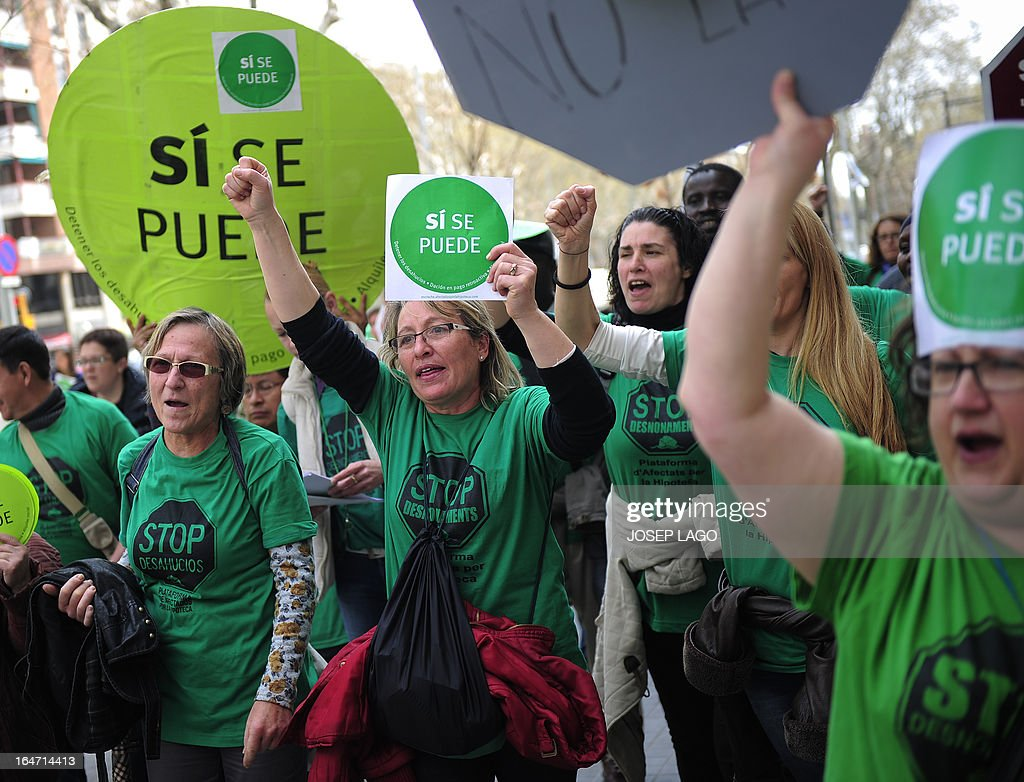 People hold placards reading 'Yes we can' during a protest by Platform for Mortgage Victims (PAH) to push for a new law to end a wave of evictions of homeowners ruined by the economic crisis, in Barcelona, on March 27, 2013. AFP PHOTO/ JOSEP LAGO
