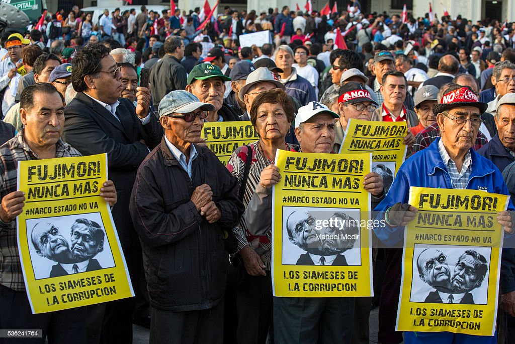 People hold placards that read in english 'Fujimori nevermore, the siameses of corruption' during a march on the streets of Lima's downtown to protest against Presidential Candidate Keiko Fujimori on May 31, 2016 in Lima, Peru. Fujimori will be competing for Peru's Presidency on the second round of the electoral voting next June 5th.