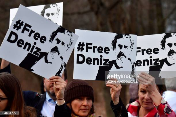 People hold placards with hashtag #FREEDENIZ to protest the detantion of German journalist Deniz Yucel in front of Turkish embassy in Berlin on...