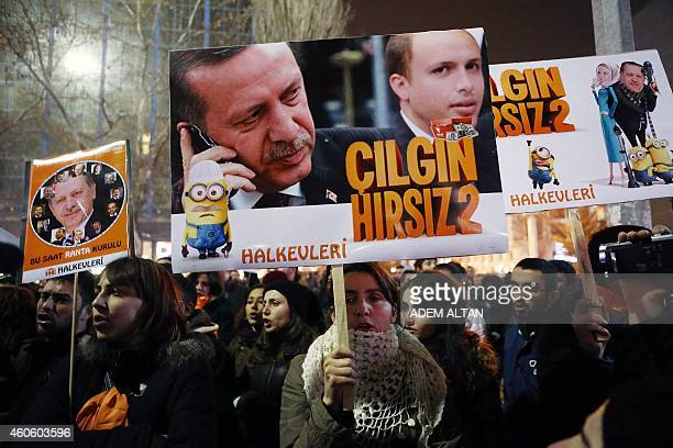 People hold placards with images of Turkish President Recep Tayyip Erdogan and his son Bilal Erdogan that read ' Crazy thief' as they protest against...
