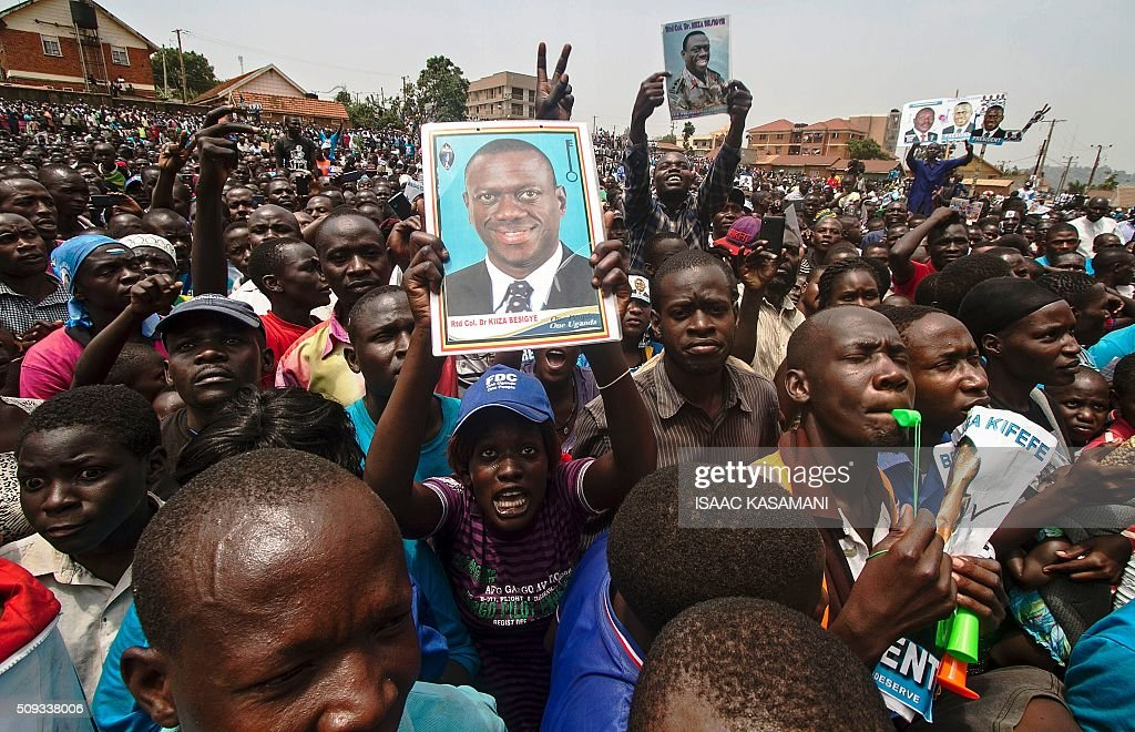 People hold portraits of Kizza Besigye, Uganda's leading opposition leader and presidential candidate, while he addresses supporters during an election rally in Kampala on February 10, 2016. Besigye will challenge incumbent President Yoweri Museveni for the fourth time when voters go to the polls on February 18, 2016. / AFP / ISAAC KASAMANI