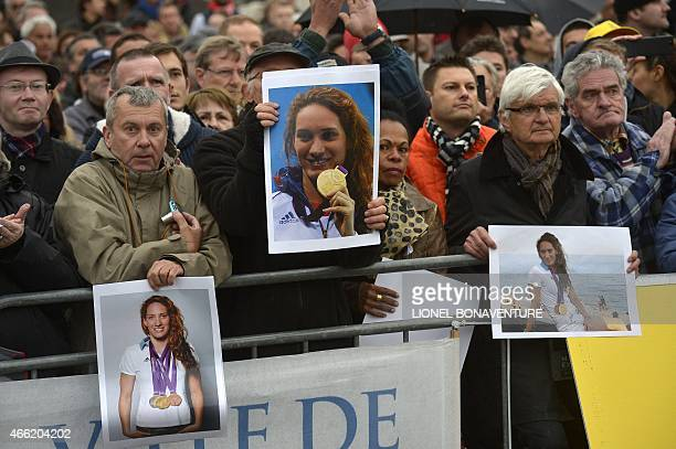 People hold portraits of late French swimming gold medallist Camille Muffat on March 14 in the southeastern French city of Nice at the end of the...