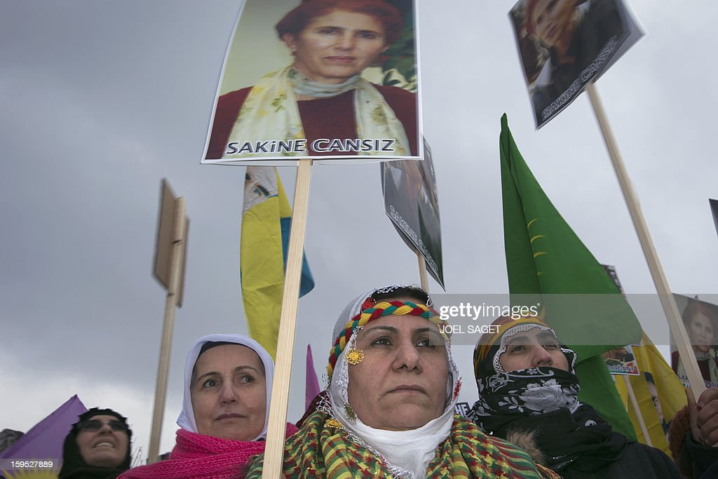 People hold portraits of late Kurdistan Workers' Party (PKK) co-founder Sakine Cansiz on january 15, 2013 in the parisian suburban city of Villiers -le-Bel during a ceremony to pay a last tribute to three top Kurdish activists killed in Paris. The three activists were found dead on January 10 at the Kurdistan Information Centre in the grimy 10th district of Paris, after last being seen alive at the centre at midday the day before.