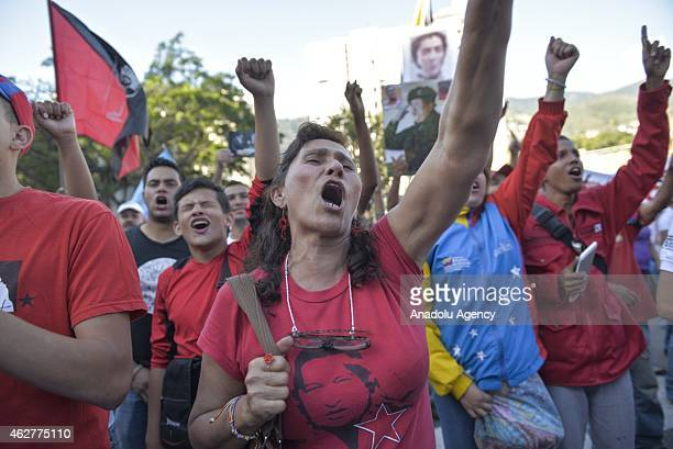 People hold posters and flags as they march during a military parade for the 23rd anniversary of attempted coup of Hugo Chavez against Carlos Andres...