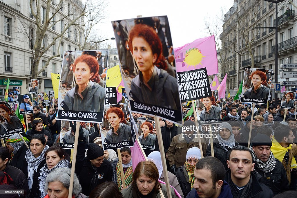 People hold posters of Sakine Cansiz, a founding member of the militant Kurdistan Workers Party (PKK), during a demonstration on January 12, 2013 in Paris, two days after Cansiz and two Kurdish activits were found shot dead at Paris Kurdistan Information Bureau. Thousands of Kurds from all over Europe are gathered in Paris today for what is expected to be an angry protest over the killing of three female activists shot dead at least three times in the head, giving further credence to the theory of an execution-style hit. Kurdish activists have accused Turkey or rogue nationalist elements in the country's military of being behind the killings. AFP PHOTO /ERIC FEFERBERG