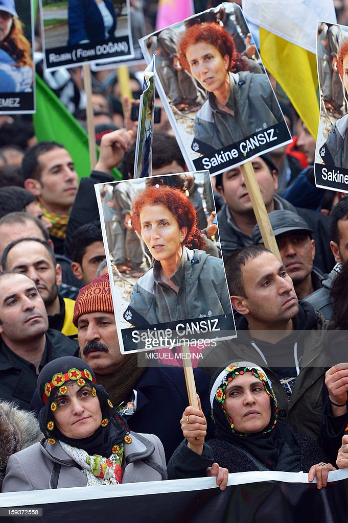 People hold posters of Sakine Cansiz, a founding member of the militant Kurdistan Workers Party (PKK), during a demonstration on January 12, 2013 in Paris, two days after Cansiz and two Kurdish activits were found shot dead at Paris Kurdistan Information Bureau. Thousands of Kurds from all over Europe are gathered in Paris today for what is expected to be an angry protest over the killing of three female activists shot dead at least three times in the head, giving further credence to the theory of an execution-style hit. Kurdish activists have accused Turkey or rogue nationalist elements in the country's military of being behind the killings. AFP PHOTO / MIGUEL MEDINA