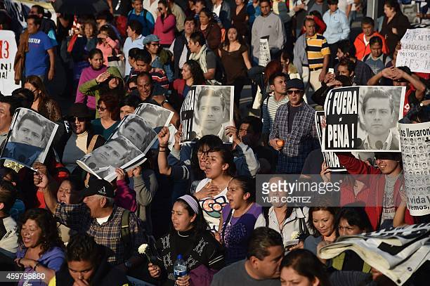 People hold posters reading 'Peña out' during a march demanding justice in the case of the 43 missing students on December 1 2014 in Mexico City...