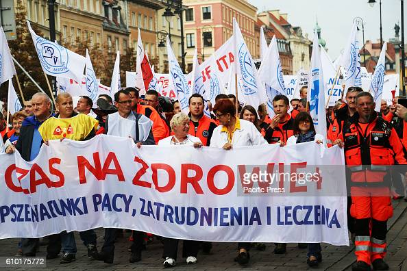 People hold posters that read ' TIme for Health ' in Warsaw Poland's old city square Thousands of medical professionals from across Poland gathered...