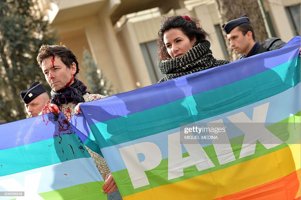 People hold rainbow flags reading 'Peace' during a protest in front of the Russian Embassy in Paris on February 10, 2016 to demand a stop to the bombardment of Aleppo and an alternative peace plan for the conflict in Syria. / AFP / MIGUEL MEDINA