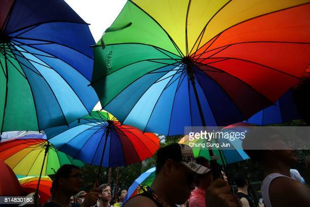 People hold rainbow pride umbrella during the Korea Queer Culture Festival 2017 in front of City hall on July 15 2017 in Seoul South Korea The annual...