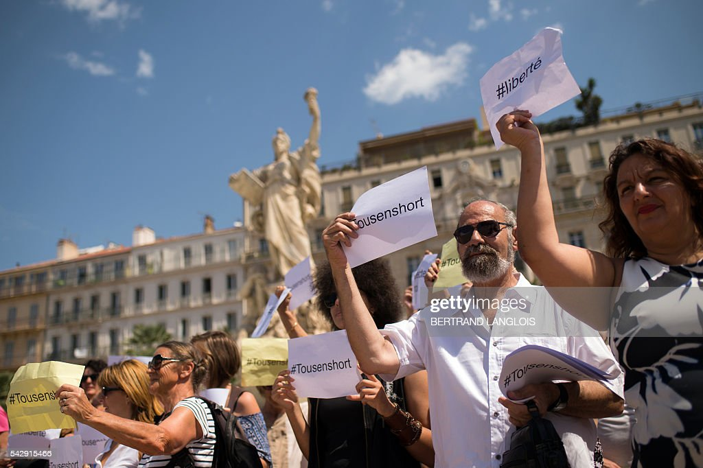 People hold sign reading 'All in shorts' and 'Freedom' during the 'Marche des Shorts' (The March of the Shorts) to show support to a young woman who was attacked in a bus because she wearing shorts, in Toulon, southeastern France, on June 25, 2016. / AFP / BERTRAND