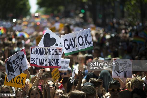 People hold sign reading ''homophobia is machismo' and 'Gay ok' as they take part in the annual Gay Pride the homosexual bisexual and transgender...
