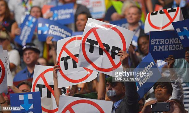 People hold signs against the Trans Pacific Partnership on Day 3 of the Democratic National Convention at the Wells Fargo Center July 27 2016 in...