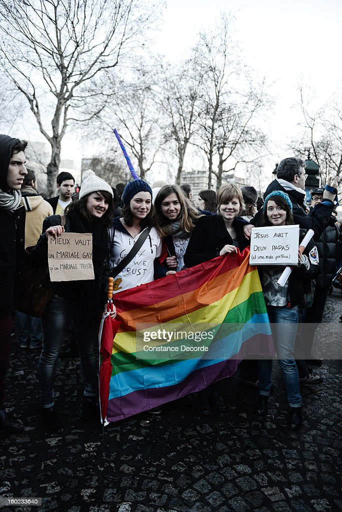 People hold signs and a rainbow flag during the marriage for all demonstration on January 28, 2013 in Paris, France. Demonstrations have shown a deep division in French society over the marriage equality on January 28, 2013 in Paris, France. The marriage equality bill, which will be debated at the French National Parliament, would not only legalize same-sex marriage and also allow gay couples to adopt, a controversial issue in the bill. French President Francois Hollande supports the legislation but faces criticism from anti-gay and religious groups, while gay rights groups have concerns of inadequacies within the bill.