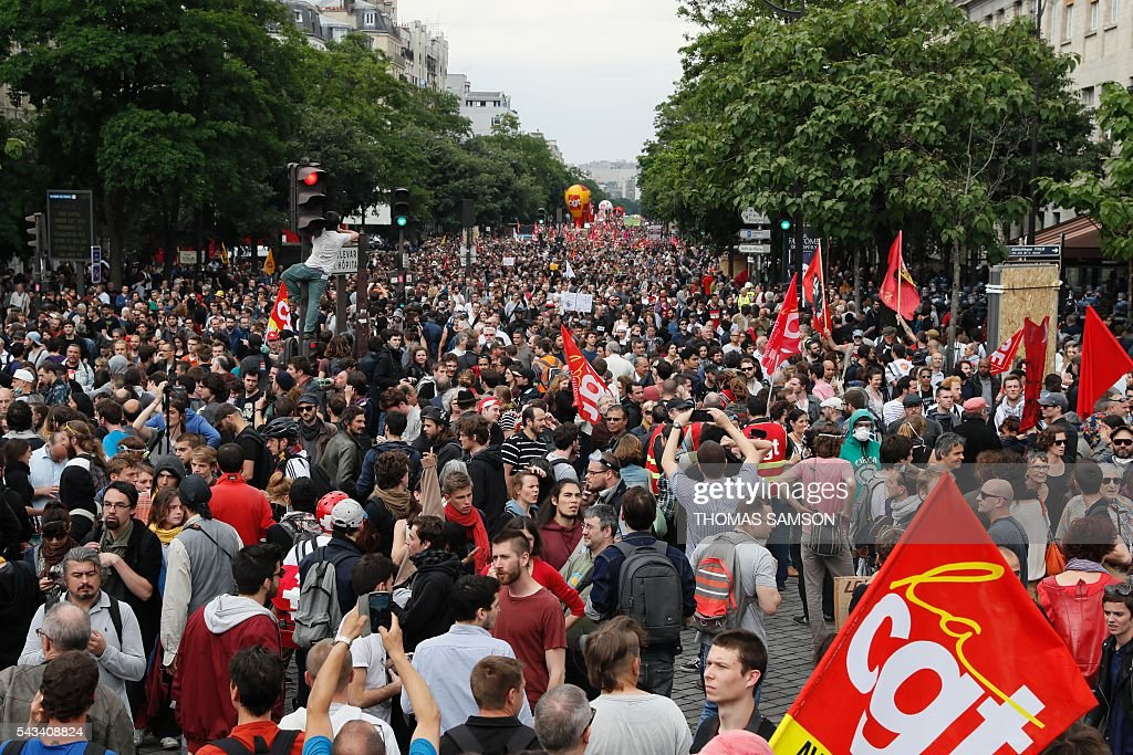 People hold signs and flags as they take part in a demonstration against controversial labour reforms, on June 28, 2016 in Paris. Unions have called repeated strikes and marches in opposition to the law, which seeks to bring down France's intractable 10-percent unemployment rate by making it easier to hire and fire workers. / AFP / Thomas SAMSON