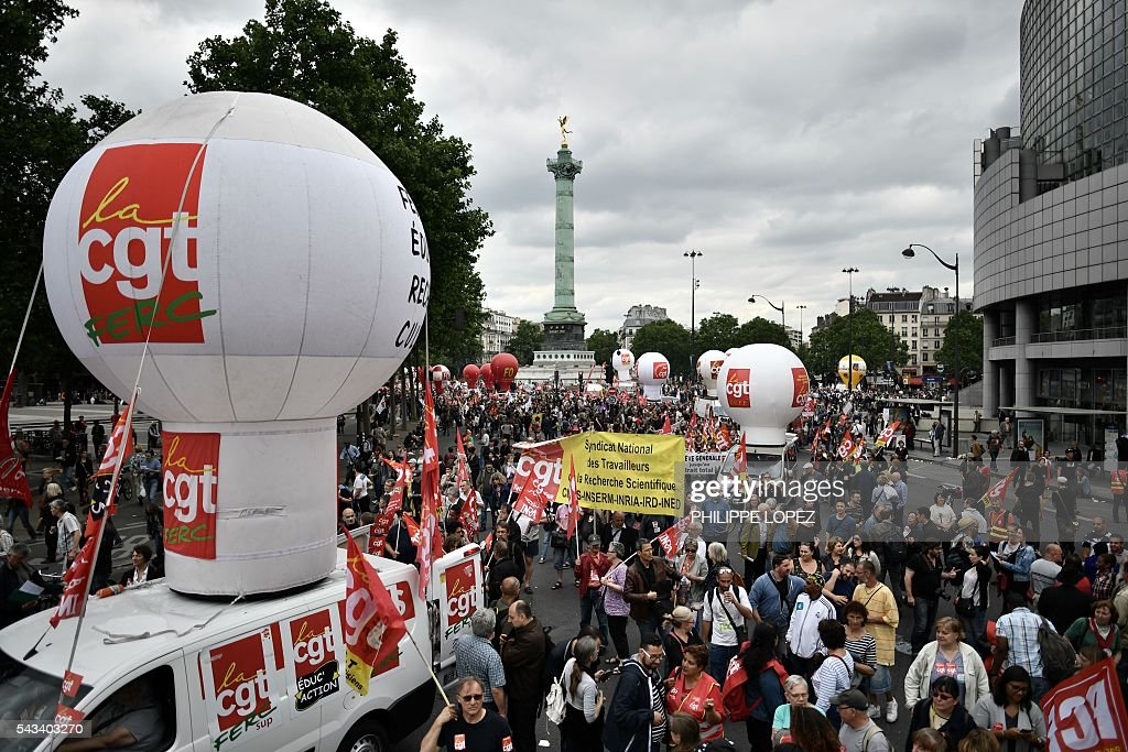 People hold signs and flags of French union CGT during a demonstration against controversial labour reforms, on June 28, 2016 on Bastille Square in Paris. Unions have called repeated strikes and marches in opposition to the law, which seeks to bring down France's intractable 10-percent unemployment rate by making it easier to hire and fire workers. / AFP / PHILIPPE
