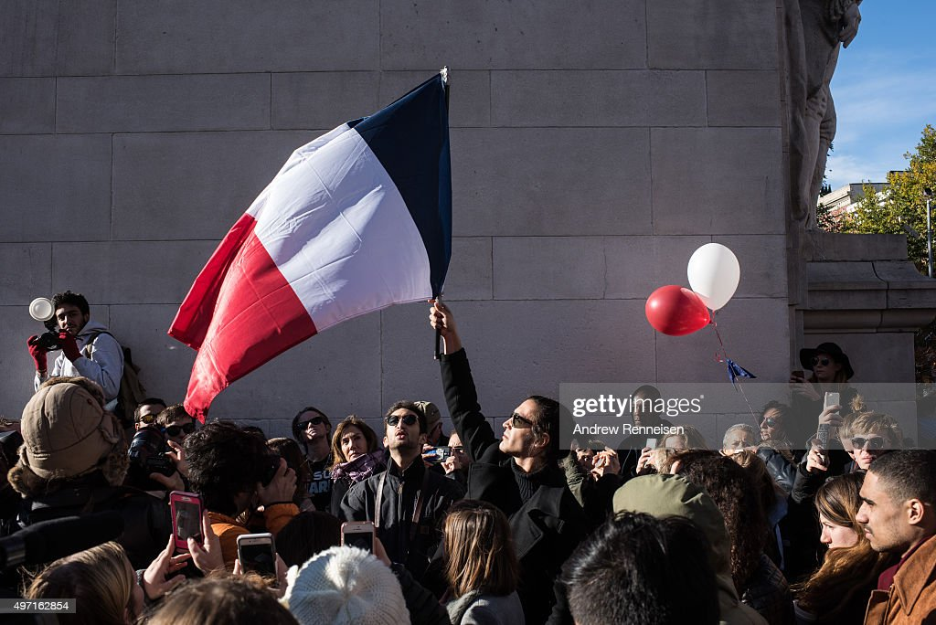 People hold signs and flags while attending a vigil held for the victims of the Paris terror attacks in Washington Square Park on November 14 2015 in...