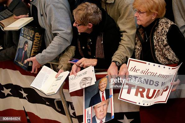People hold signs and pictures as they wait to greet Republican presidential candidate Donald Trump during a campaign event January 23 2016 in Pella...
