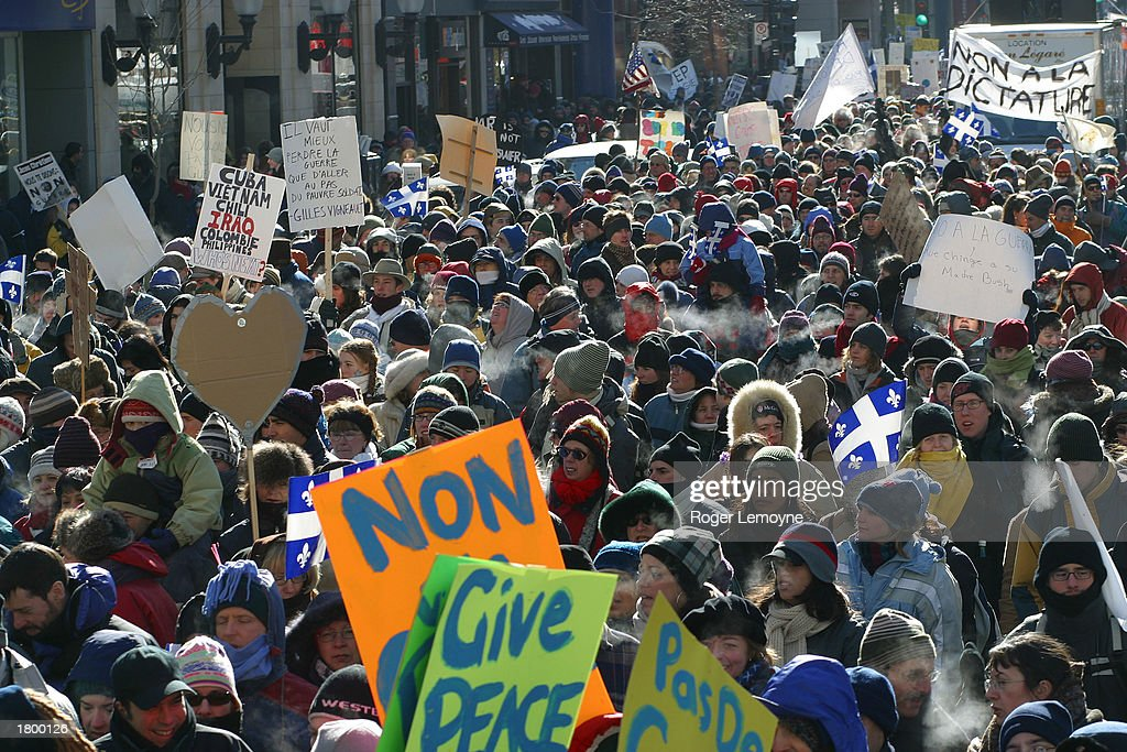 People hold signs and wave flags during a demonstration against a possible war on Iraq February 15, 2003 in Montreal, Canada. Tens of thousands of protesters braved cold temperatures at the rally that coincided with peace demonstrations around the world.