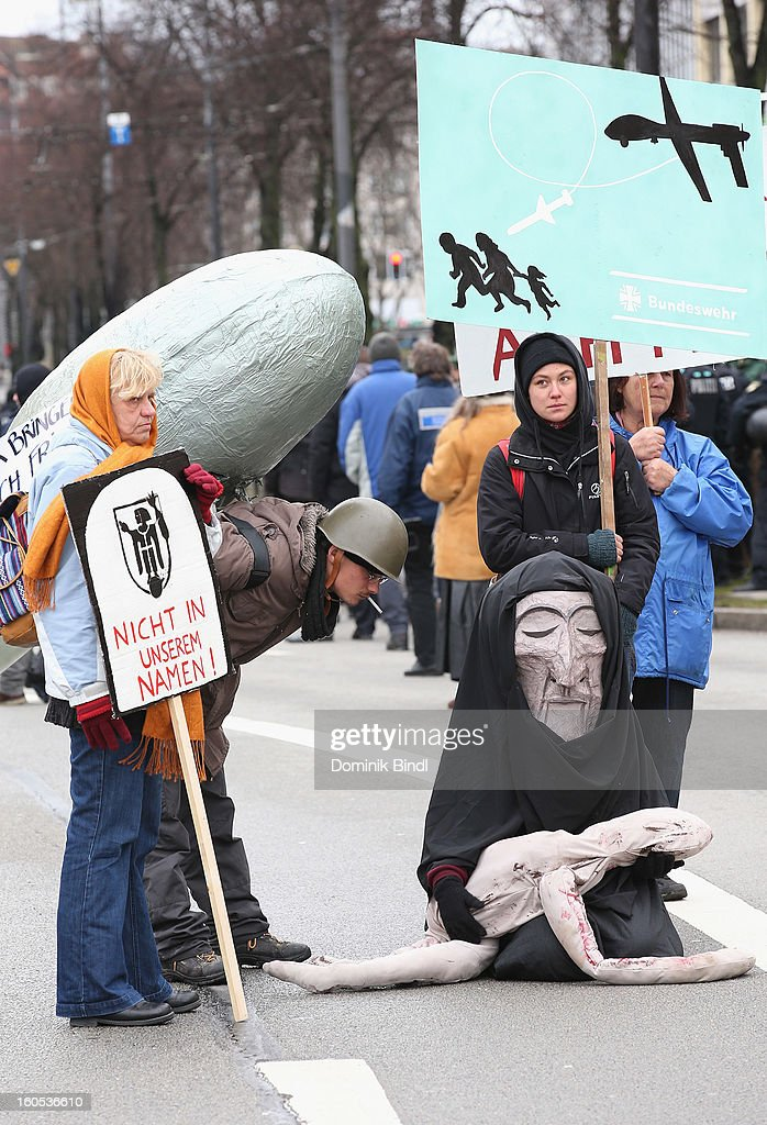 People hold signs and wear costumes as they demonstrate during a protest against the Munich Security Conference in the city centre on February 2, 2013 in Munich, Germany. The Munich Security Conference brings together senior figures from around the world to engage in an intensive debate on current and future security challenges and remains the most important independent forum for the exchange of views by international security policy decision-makers.