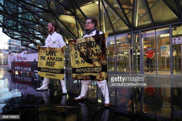 People hold signs as Greenpeace activisits pour molasse in front of French oil giant Total headquarters on March 27 2017 in La Defense district...