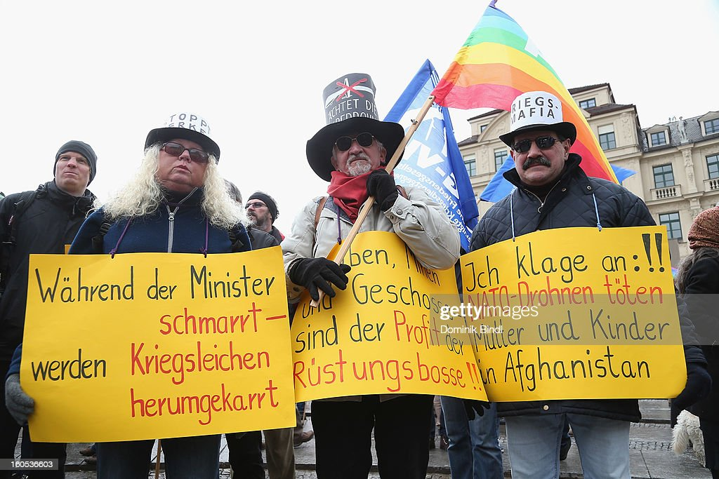 People hold signs as they demonstrate during a protest against the Munich Security Conference in the city centre on February 2, 2013 in Munich, Germany. The Munich Security Conference brings together senior figures from around the world to engage in an intensive debate on current and future security challenges and remains the most important independent forum for the exchange of views by international security policy decision-makers.