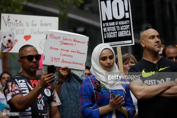 People hold signs at a vigil August 13 2017 in Chicago Illinois for the victims in the previous day's violent clashes in Charlottesville Virginia...