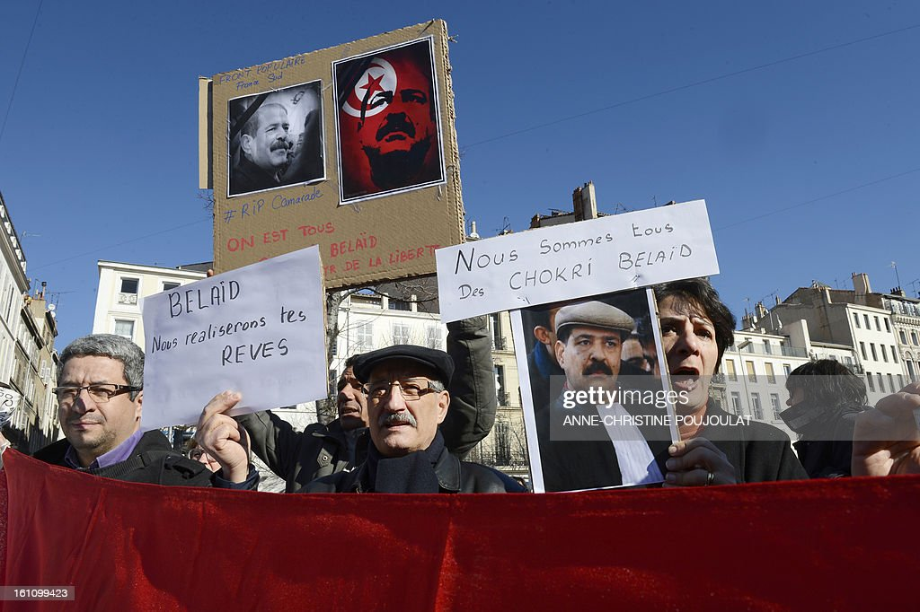 People hold signs bearing pictures of murdered opposition figure Chokri Belaid and reading 'We are all some Chokri Belaid' (at right) and 'Belaid, we are fulfilling your dreams' during a protest to pay tribute to Belaid on February 9, 2013, in Marseille, southern France. The shooting of Belaid, a leftist leader and outspoken government critic by a lone, hooded gunman on February 6, 2013 plunged Tunisia into new post-revolt turmoil as tension and division within the Ennahda party itself intensified.