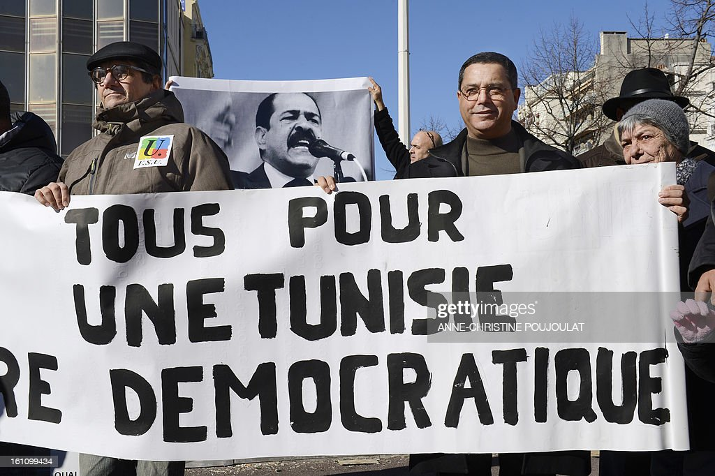 People hold signs bearing pictures of murdered opposition figure Chokri Belaid and reading 'All, for a democratic Tunisia' during a protest to pay tribute to Belaid on February 9, 2013, in Marseille, southern France. The shooting of Belaid, a leftist leader and outspoken government critic by a lone, hooded gunman on February 6, 2013 plunged Tunisia into new post-revolt turmoil as tension and division within the Ennahda party itself intensified.