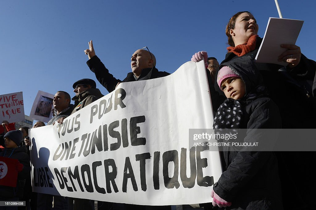 People hold signs bearing pictures of murdered opposition figure Chokri Belaid and reading 'All for a democratic Tunisia' during a protest to pay tribute to Belaid on February 9, 2013, in Marseille, southern France. The shooting of Belaid, a leftist leader and outspoken government critic by a lone, hooded gunman on February 6, 2013 plunged Tunisia into new post-revolt turmoil as tension and division within the Ennahda party itself intensified.