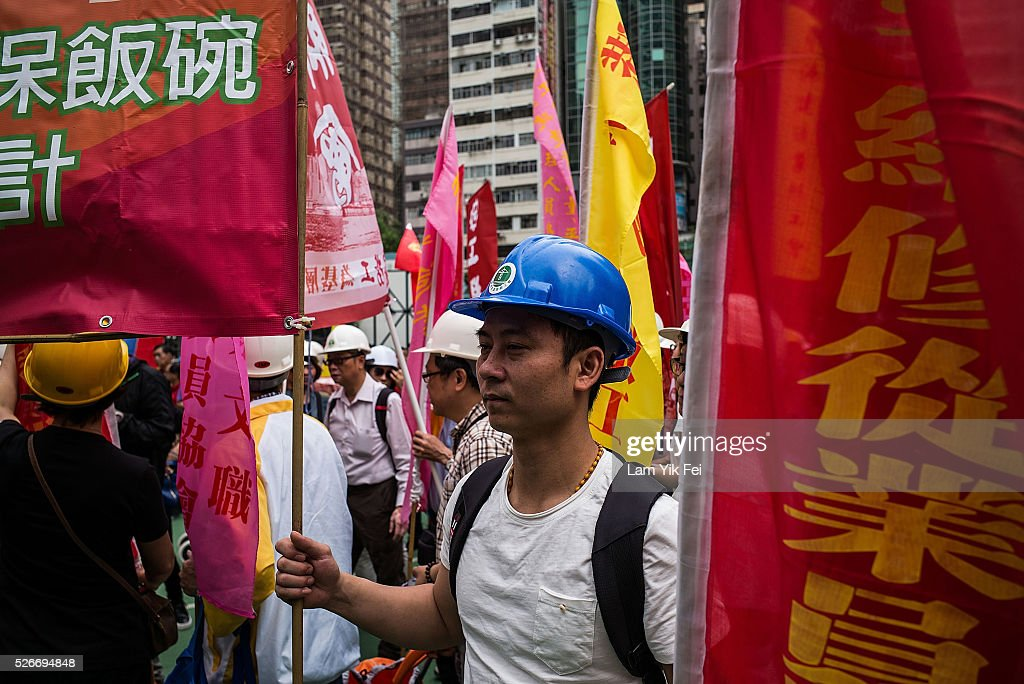 People hold signs during a Labour Day rally on May 1, 2016 in Hong Kong, Hong Kong. Hundreds gathered in Hong Kong on Labor Day, demanding better workers' rights while voicing out their resentment against mainland travellers in Hong Kong.
