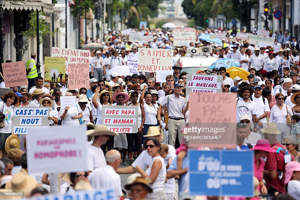 People hold signs during a protest against same-sex marriage, on January 13, 2013 in Saint-Denis de la Reunion, on the French Indian Ocean island of Reunion. Tens of thousands march in Paris on January 13 to denounce government plans to legalise same-sex marriage and adoption which have angered many Catholics and Muslims, France's two main faiths, as well as the right-wing opposition. The French parliament is to debate the bill -- one of the key electoral pledges of Socialist President -- at the end of this month.