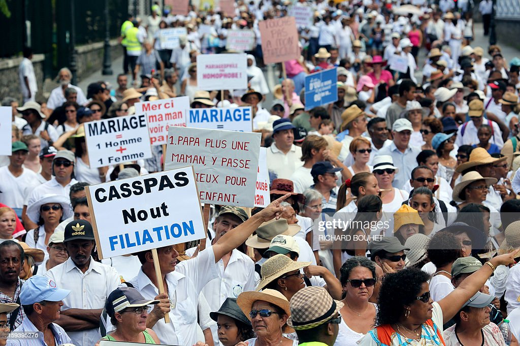 People hold signs during a protest against same-sex marriage, on January 13, 2013 in Saint-Denis de la Reunion, on the French Indian Ocean island of Reunion. Tens of thousands march in Paris on January 13 to denounce government plans to legalise same-sex marriage and adoption which have angered many Catholics and Muslims, France's two main faiths, as well as the right-wing opposition. The French parliament is to debate the bill -- one of the key electoral pledges of Socialist President -- at the end of this month. AFP PHOTO/RICHARD BOUHET