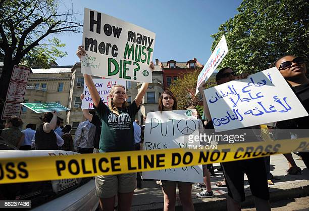 People hold signs during a protest and an act of civil disobedience by US Congressmen to protest the Sudanese government's ongoing genocide in Darfur...