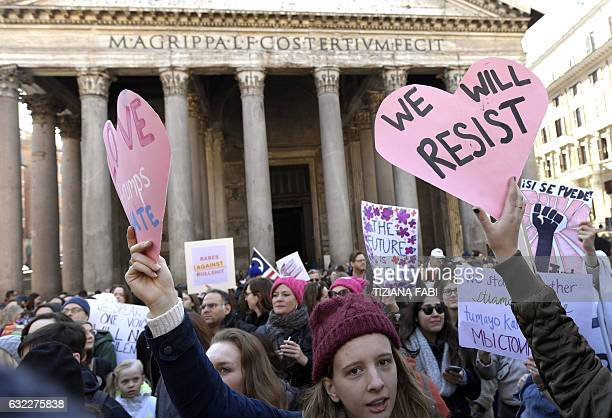 People hold signs during a rally against US newly swornin President Donald Trump in Rome on January 21 a day after Trump's inauguration Hundreds of...