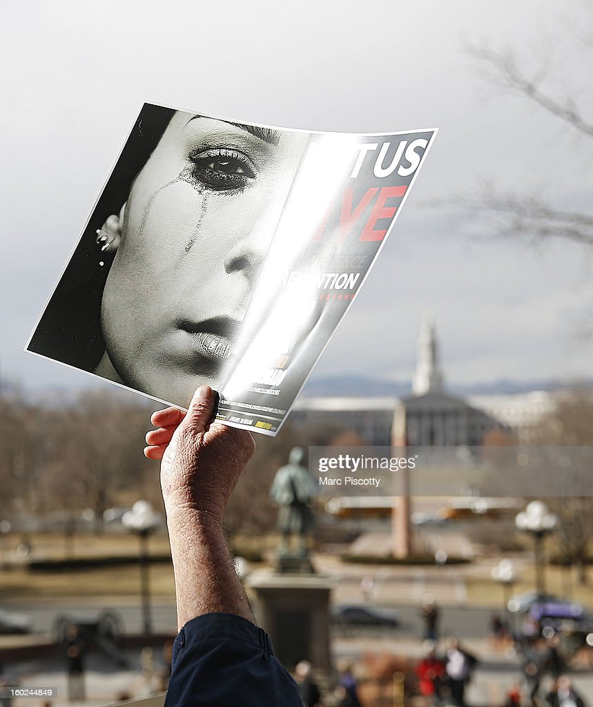 People hold signs for a 'Let Us Live' gun violence prevention rally on the steps of the Colorado State Capitol on January 28, 2013 in Denver, Colorado. The event was organized by Together Colorado, a non-partisan, multi-racial, multi-faith community organizing group.