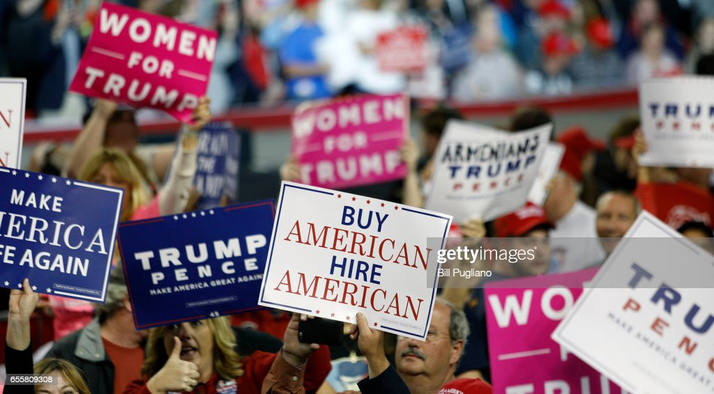 People hold signs in support of U.S. President Donald Trump before a rally in Freedom Hall at the Kentucky Exposition Center March 20th, 2017 in Louisville, Kentucky.