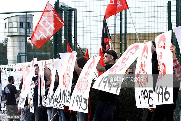 People hold signs marking the years that Lebanese activist Georges Ibrahim Abdallah spent in prison as they take part in a protest calling for his...