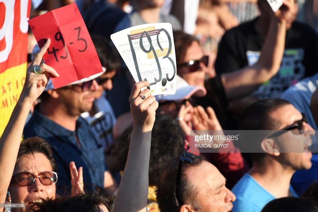 People hold signs reading '49.3' during the speech of the French Prime Minister for the inauguration of the tram line 4 on July 1, 2016, in Montpellier, southern France. / AFP / PASCAL